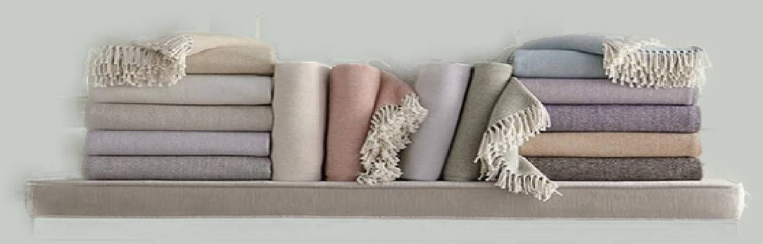 Luxury pastel colored throw blankets stacked on a shelf