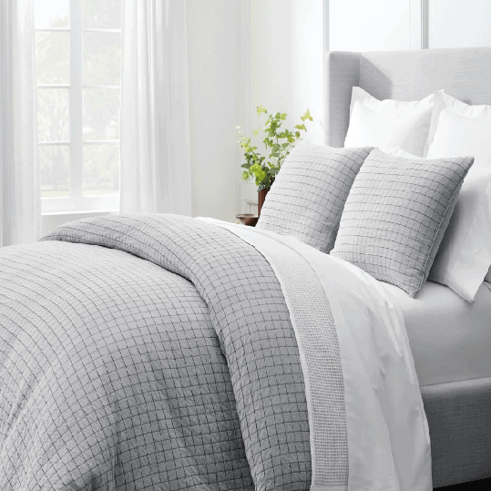 Gray and white Boll & Branch comforter and sheets on bed