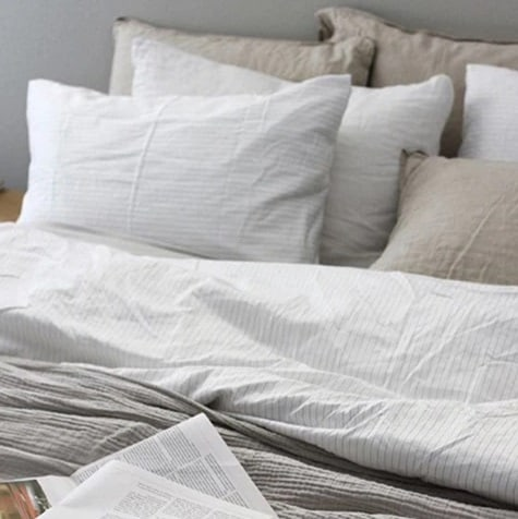 Light colored Brooklinen sheets and pillows on a bed.