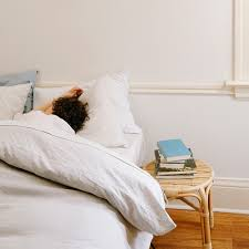 Person sleeping in bed with Coyuchi bedding.
