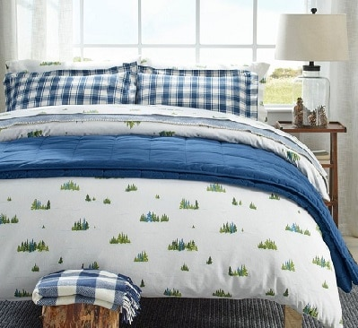 Blue, white, green various patterned flannel L.L. Bean sheets on a bed.
