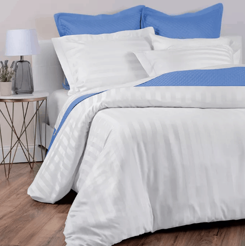 Blue and white pillows and bedding on a bed.