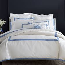 Elegant white bedding on bed with blue detailing.