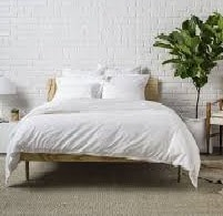 Modern looking white sheets on a bed.