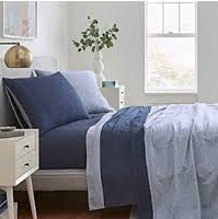 Dark and light blue sheets and pillows on a bed