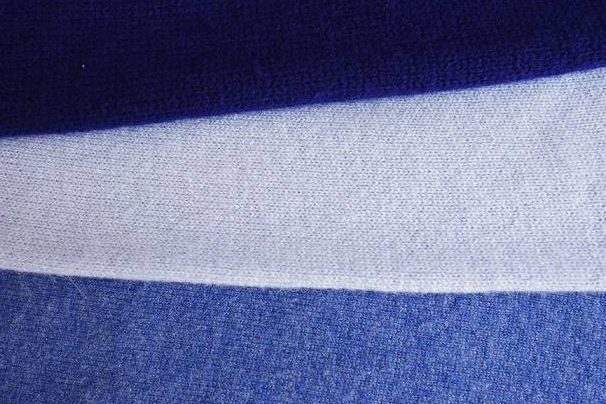 Close up of three shades of blue cashmere sweaters.