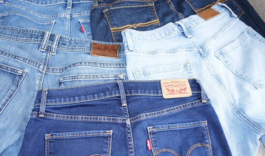 A few different pairs of jeans with back pockets showing